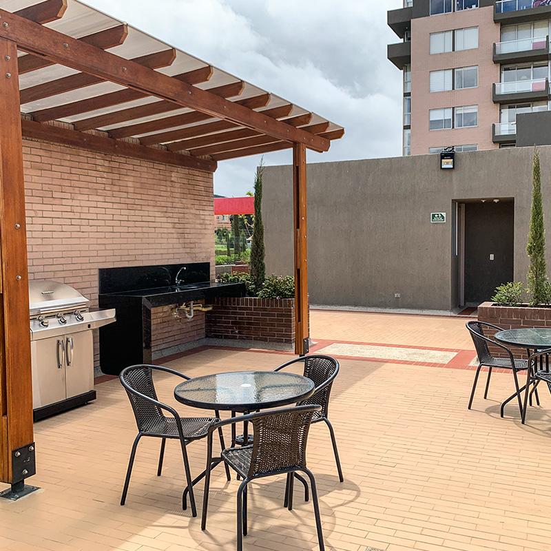 Terraza con mesas y zona BBQ del proyecto Ciudad Hayuelos Santiago de Tunja